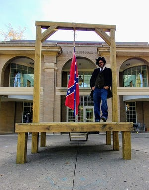 """Artist John Sims stands with his art installation, """"The Proper Way to Hang a Confederate Flag."""""""