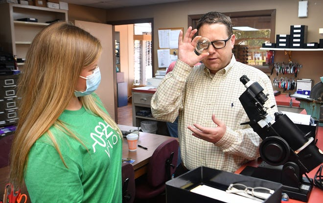 Greg Deatherage of Deatherage Opticians shows McKinley Lee how eyeglass lenses work. Lee founded a nonrpofit to help students from low-income families get free eye exams and glasses.
