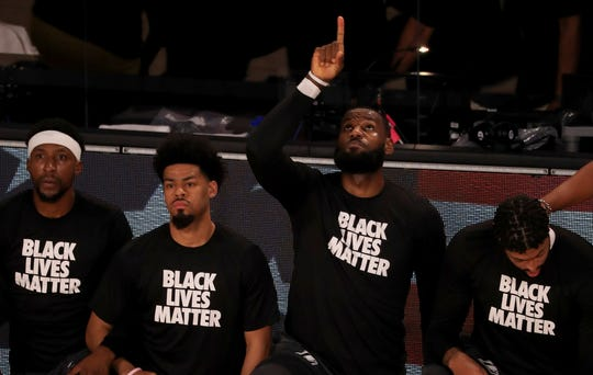 LeBron James wears a Black Lives Matter shirt as he points up and kneels with his teammates during the national anthem before the opening game in the NBA bubble.