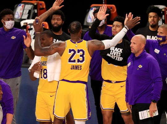 July 30: LeBron James and the Lakers celebrate after edging the Clippers in their opening game of the season restart.