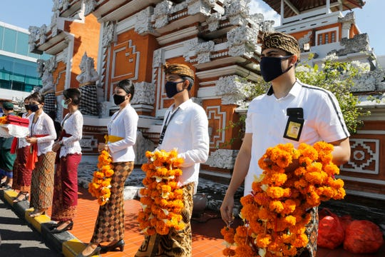 Airport officers wearing face masks line up as they hold flowers to welcome passengers at the Bali airport in Indonesia on July 31, 2020. Bali reopened for domestic tourists after months of lockdown due to a new coronavirus.