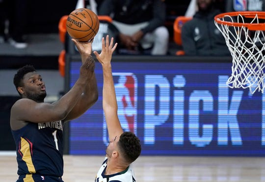 New Orleans rookie Zion Williamson, left, shoots over Utah's Georges Niang.