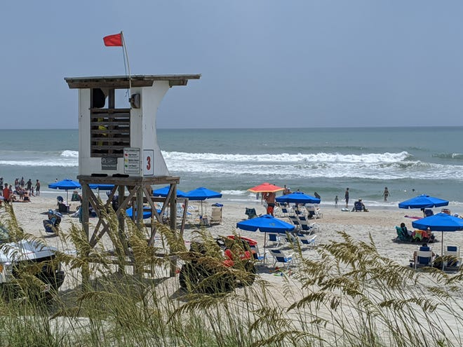 Red warning flags were out in Wrightsville Beach on Saturday due to the heavy surf and danger of rip currents as the outer swells of Hurricane Isaias began impacting the Carolinas.