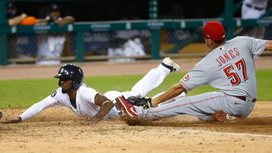 Detroit Tigers' Travis Demeritte beats the tag of Cincinnati Reds relief pitcher Nate Jones (57) to score at home plate on a wild pitch in the seventh inning.