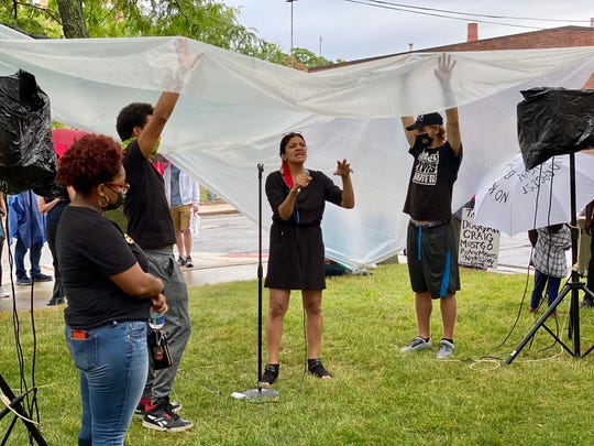 Protesters help keep U.S. Rep. Rashida Tlaib, D-Detroit, dry during rain as she spoke to demonstrators on the 65th day of protests at Mt. Elliott Park in Detroit, Aug. 1, 2020.