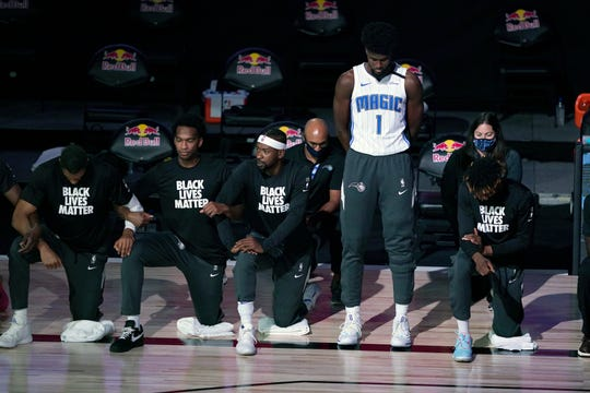Orlando Magic's Jonathan Isaac (1) stands as others kneel before the start of an NBA game Friday between the Brooklyn Nets and the Orlando Magic in Lake Buena Vista, Fla.