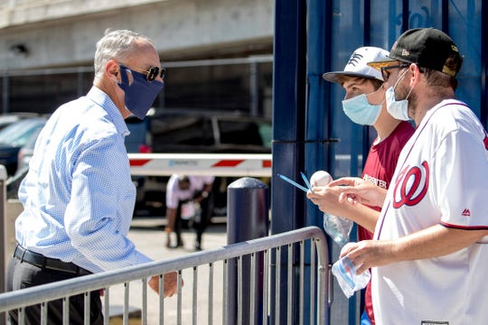 MLB Commissioner Rob Manfred, left, speaks with fans as he arrives at Nationals Park for the New York Yankees and the Washington Nationals on Thursday.