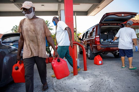 A resident walks with containers filled with gasoline at Cooper's gas station before the arrival of Hurricane Isaias in Freeport, Grand Bahama, Bahamas, Friday, July 31, 2020.