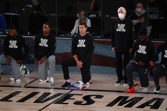 San Antonio Spurs head coach Gregg Popovich, fourth from left, stands while wearing a mask while Sacramento Kings head coach Luke Walton, center, kneels with players before an NBA game Friday.