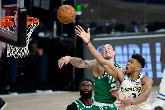 Milwaukee Bucks' Giannis Antetokounmpo, right, heads to the basket as Boston Celtics' Daniel Theis defends during the second half Friday in Lake Buena Vista, Fla.