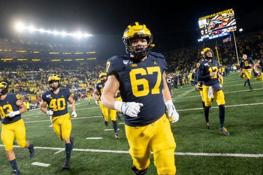 Michigan defensive lineman Jess Speight runs with his teammates to celebrate after beating Notre Dame at Michigan Stadium in 2019.