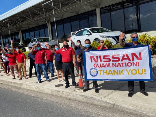 Nissan Guam employees celebrate in this file photo after learning the company set the world record for the longest parade of Nissan cars.