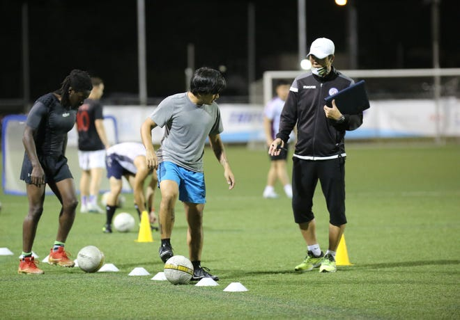 "Guam Football Association ""D"" Coaching Certificate Course participant Jordan Salinas, in gray, listens to course instructor Sang Hoon Kim as he explains ways to improve technique during a practical session at the GFA National Training Center July 31, 2020."