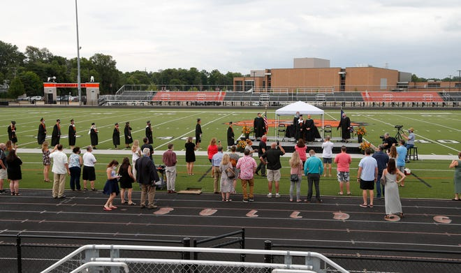 Graduates line up to get their diplomas during Brighton's outdoor socially distanced graduation ceremony at their football stadium, Saturday, Aug. 01, 2020, in Brighton, Mich.