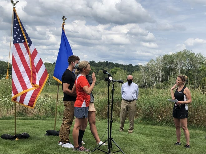 Wisconsin Supreme Court Justice Jill Karofsky is sworn in by fellow Justice Rebecca Dallet, right, as her children, Danny and Daphne, and former Gov. Jim Doyle look on. Karofsky took the oath Saturday in Basco during a break in a 100-mile run.