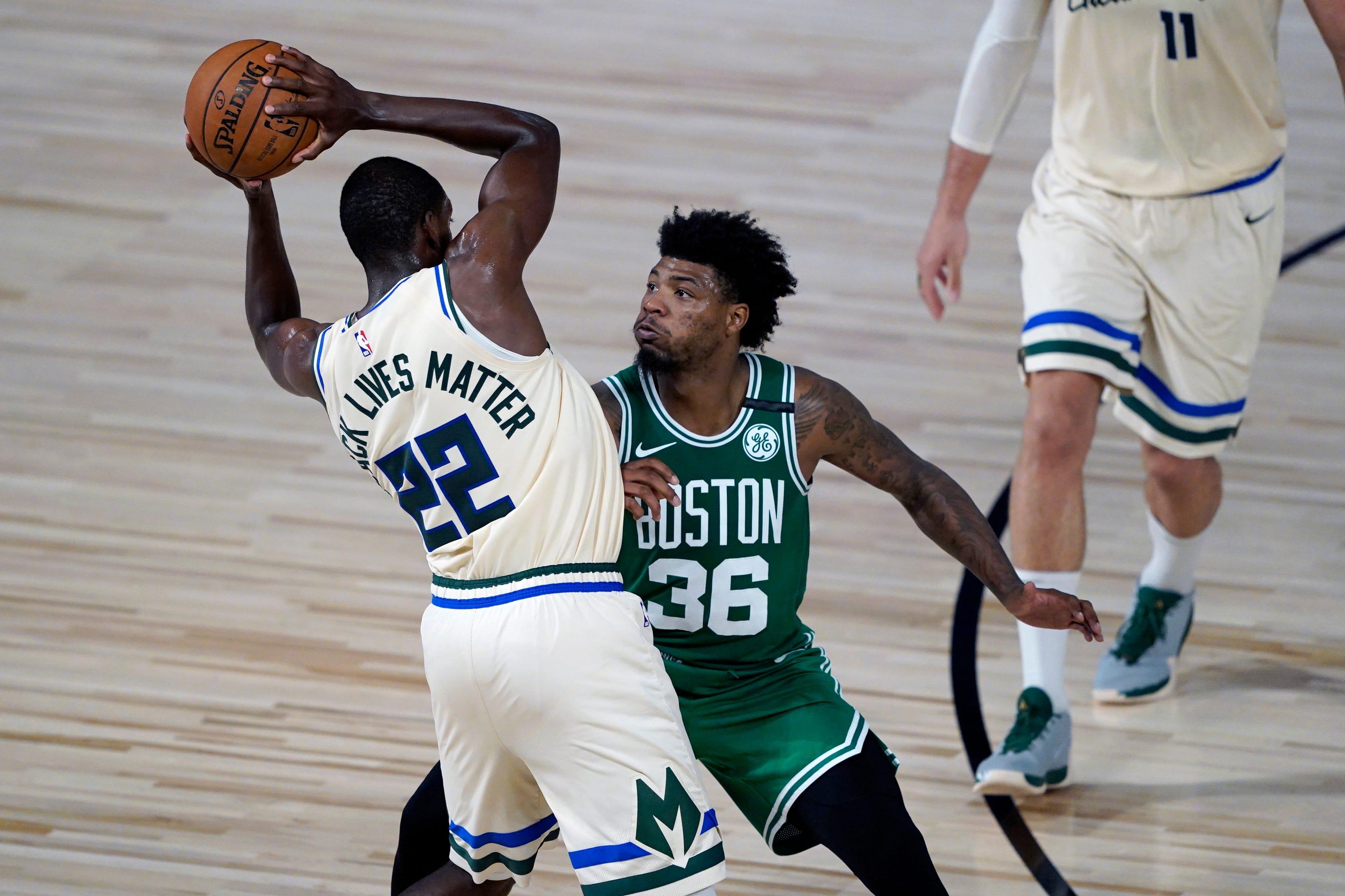 The Celtics' Marcus Smart closely guards the Bucks' Khris Middleton.