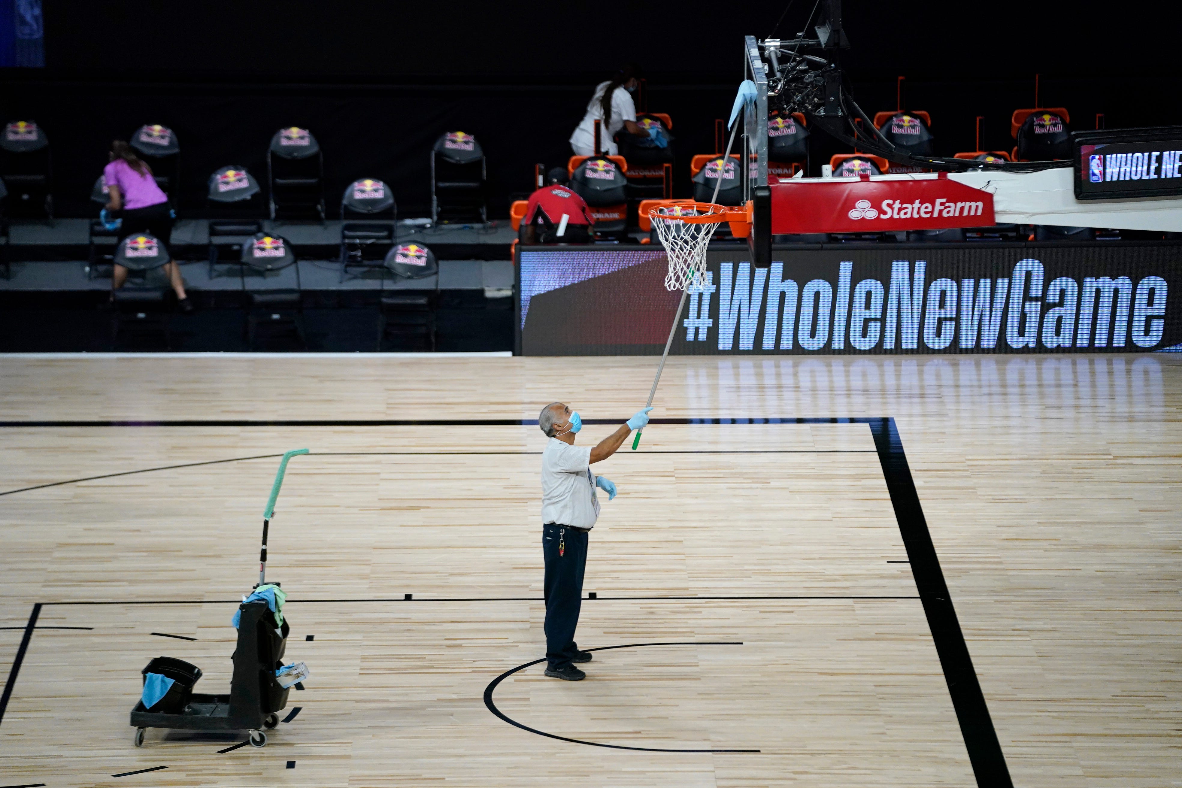 A worker cleans the backboard during the game between the Celtics and Bucks.