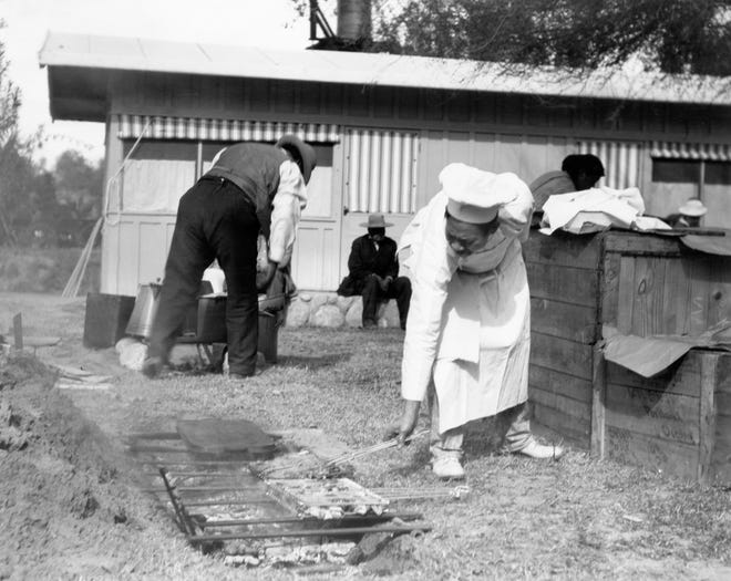Chinese cook tends to an outdoor BBQ at The Desert Inn in this undated photo.