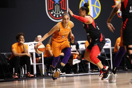 Phoenix Mercury guard Diana Taurasi (left)  with ball against the Las Vegas Aces.