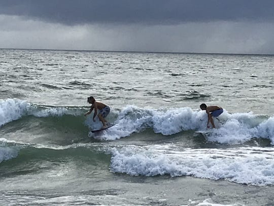 Two intrepid (perhaps foolhardy) surfers catch a wave early Saturday, Aug. 1, 2020, at Chastain Beach near the south end of Hutchinson Island at Stuart. The rain seen in the background hit the beach around 9:15 a.m.