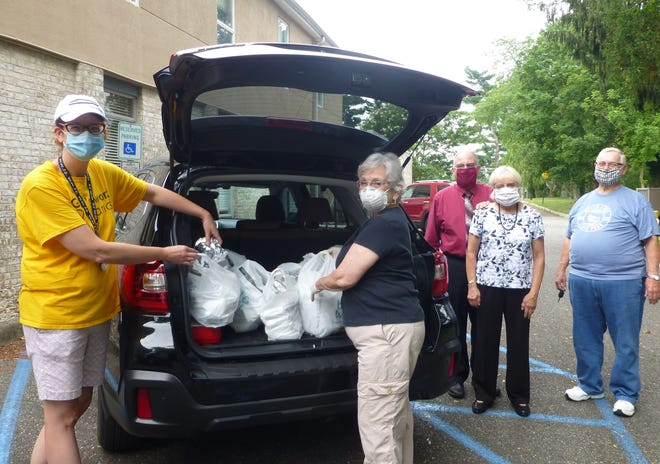 Members of the Lutheran Church of the Redeemer, Vineland, load peanut butter and jelly sandwiches into a vehicle for transportation to the Vineland Soup Kitchen. Church members prepare 200 sandwiches each week to help community members in need.