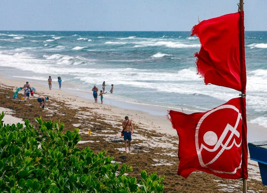 Red no swimming flags fly at Lantana Municipal Beach as Isaias approaches the Florida coast Saturday.