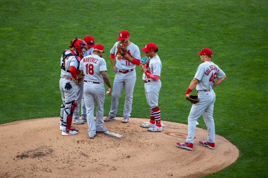 Cardinals players meet on mound for a conference.
