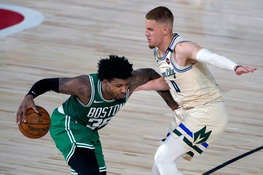 Boston's Marcus Smart, driving against Donte DiVincenzo, scored 23 points in a 119-112 loss to Milwaukee on Friday.