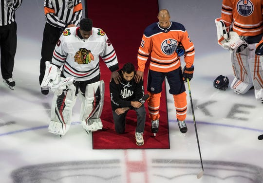 Minnesota Wild's Matt Dumba takes a knee during the national anthem while flanked by Edmonton Oilers' Darnell Nurse, right, and Chicago Blackhawks' Malcolm Subban.