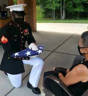 "A U.S. Marine Corps Honor Guard soldier presents the American flag to Dorothy Smith of Fort Lee during the military funeral for Smith's brother veteran Herbert L. ""Mickey"" Bowles at the Quantico National Cemetery July 9, 2020 in Triangle, Va. Bowles succumbed to COVID-19 April 4, 2020 in Petersburg, Va."