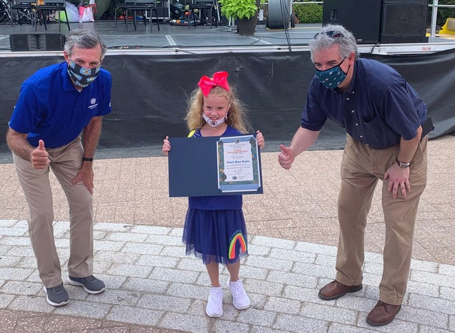 Gov. John Carney (left) and DNREC Secretary Shawn Garvin recognize Charli Rose Evans, of Laurel, as the Elementary School Young Environmentalist of the Year at the Delaware State Fair.