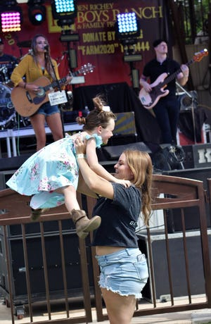 Kynzie Colomery is lifted into the air the air by Cheyenne Davis, her older sister, while Bri Bagwell plays Saturday at the Farm Raise Music Fest at the Back Porch of Texas.