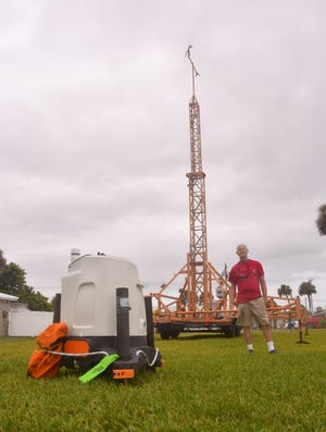Steven Lazarus, a meteorologist and Florida Tech professor, stands alongside a lidar device and a portable weather tower Sunday morning at the Sand Castle condominium complex in Satellite Beach.