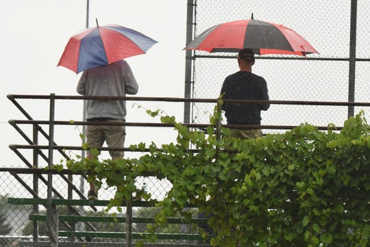 People with umbrellas watch a baseball game as steady rain falls at Memorial Park in Royal Oak on Saturday, August 1, 2020.