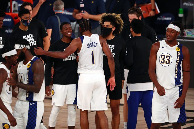 Aug 1, 2020; Lake Buena Vista, Florida, USA; The Indiana Pacers celebrate with forward T.J. Warren (1) after beating the Philadelphia 76ers in a NBA basketball game at Visa Athletic Center. Mandatory Credit: Kim Klement-USA TODAY Sports