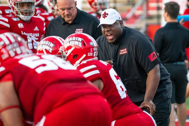 UL assistant football coach D.J. Looney (in hat), shown here working with players before a game against Appalachian State last October, passed away after having a heart attack Saturday.