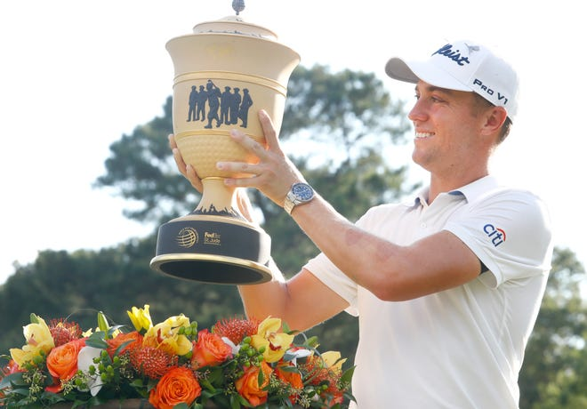 Justin Thomas accepts the trophy after winning the WGC-FedEx St. Jude Invitational golf tournament at TPC Southwind on Sunday with a final score of 13 under.