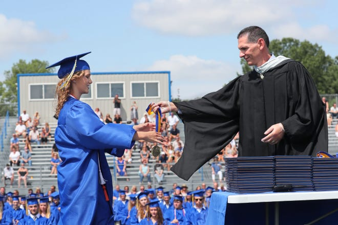 Sophia Knudsen, left, accepts her award from principal James Darin, for being one of the class valedictorians at Mukwonago High School's graduation ceremony on Sunday, Aug. 2, 2020. Many area school districts are holding more traditional graduation ceremonies this year.