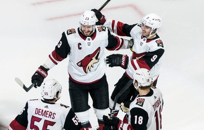Arizona Coyotes' Oliver Ekman-Larsson (23), Clayton Keller (9), Jason Demers (55) and Christian Dvorak (18) celebrate a goal against the Nashville Predators during first-period NHL hockey Stanley Cup qualifying round game action in Edmonton, Alberta, Sunday, Aug. 2, 2020. (Jason Franson/The Canadian Press via AP)