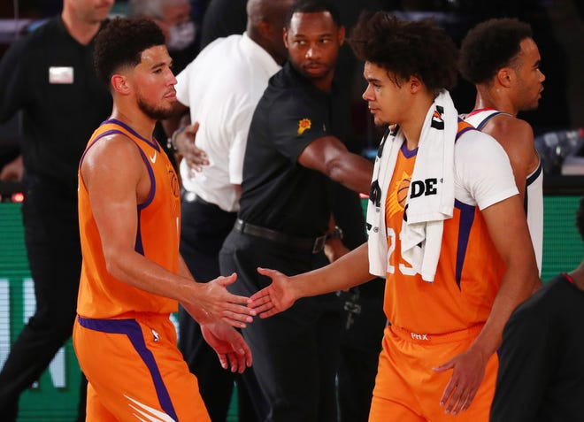 Phoenix Suns guard Devin Booker (1) slaps hands with forward Cameron Johnson (23) after defeating the Washington Wizards in an NBA basketball game in Lake Buena Vista, Fla., Friday, July 31, 2020. (Kim Klement/Pool Photo via AP).