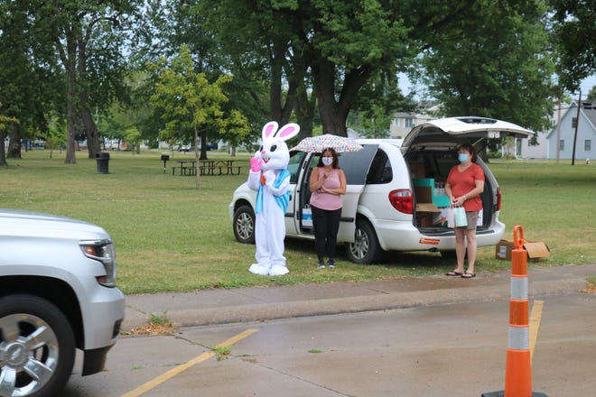 "Volunteers work as part of the Easter Bunny's ""pit crew"" to hand out treats during the drive-thru Easter Egg hunt at Lakeview Park on Saturday."