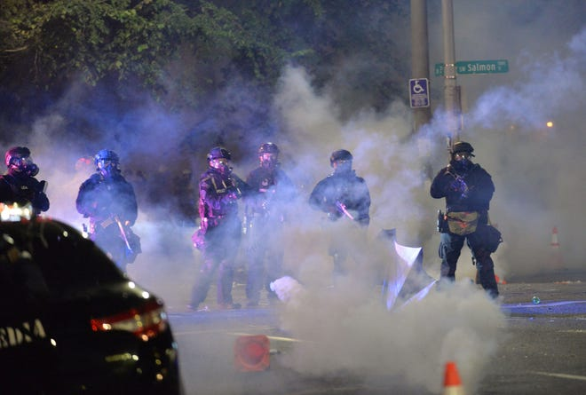 """Security personnel stand in a cloud of tear gas in Portland, Oregon early Sunday, July 26, 2020, as protests continue across the United States following the death in Minneapolis of unarmed African-American George Floyd. Police and federal agents fired tear gas and forcefully dispersed protesters in Portland amid President Donald Trump's heavily-criticized """"surge"""" of security forces to major cities. The city, the biggest in the state of Oregon, has seen nightly protests against racism and police brutality for nearly two months, initially sparked by the death of unarmed African American George Floyd at the hands of police in Minnesota (Ankur Dholakia/AFP/Getty Images/TNS)"""