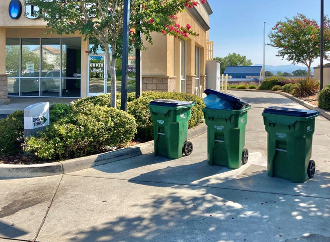 Trash bins block the entrance to the drive-through at the Starbucks store in Anderson, which shut down recently after an employee tested positive for COVID-19.