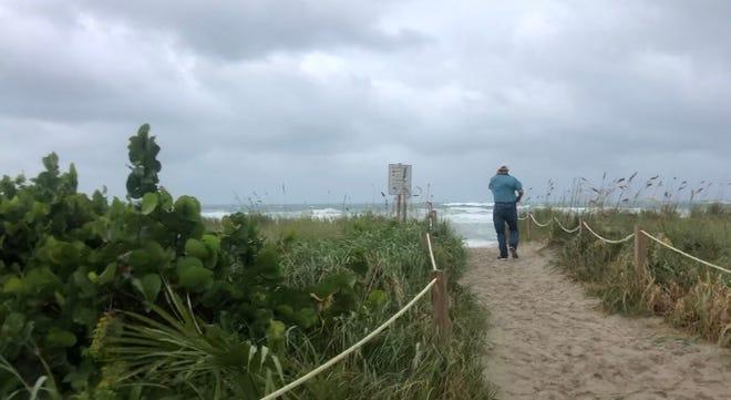 David Comstozk, 72, of Port St. Lucie, walks toward an empty Waveland Beach as Tropical Storm Isaias nears the Treasure Coast.