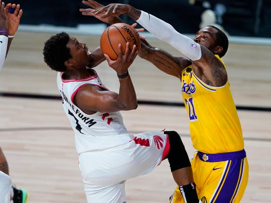 Toronto Raptors guard Kyle Lowry shoots the ball between Los Angeles Lakers guard JR Smith (21) and forward LeBron James.