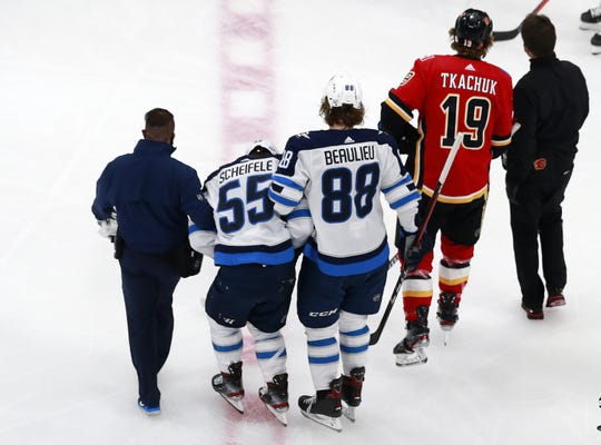 Winnipeg Jets forward Mark Scheifele is helped off the ice after suffering an injury in Game 1 against the Calgary Flames.