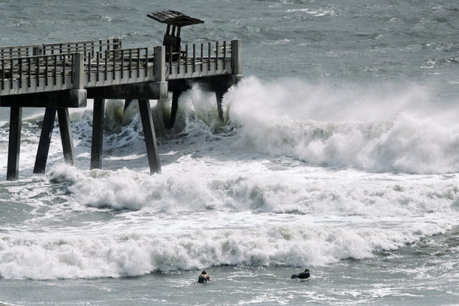 A pair of surfers paddle out as incoming waves break at the end of the Jacksonville Beach Fishing Pier on Monday morning. Tropical Storm Isaias was heading toward the Carolinas, where it was expected to strengthen to hurricane status.