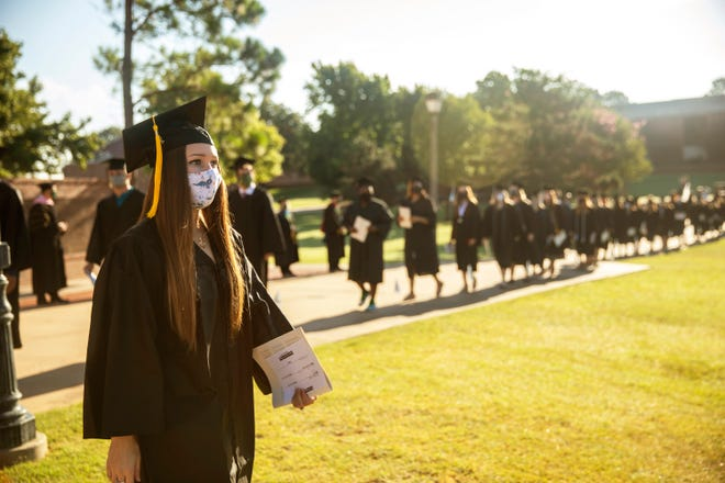 Students take their symbolic final walk across campus to the commencement ceremony.