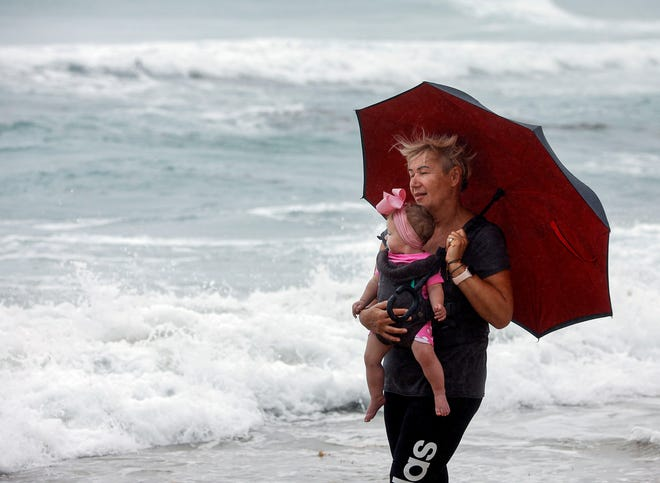 Joanna Janczak tries to stay dry at a Lake Worth, Fla., beach with 8 month-old Sophia in her arms as Isaias passes by Florida's east coast Sunday. [Damon Higgins/The Palm Beach Post via AP]