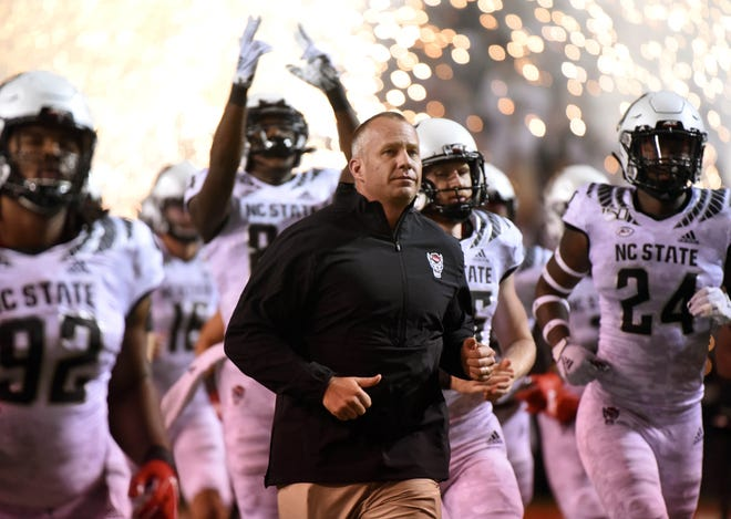 Oct 10, 2019; Raleigh, NC, USA; North Carolina State Wolfpack head coach Dave Doeren (center) leads his team onto the field prior to a game against the Syracuse Orange at Carter-Finley Stadium. Mandatory Credit: Rob Kinnan-USA TODAY Sports